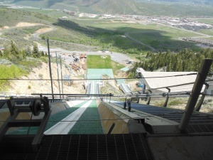 View from top of ski jump, skis go in white tracks on jump
