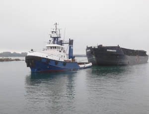 Tug towing barge used to haul steel coils from steel plant to Detroit