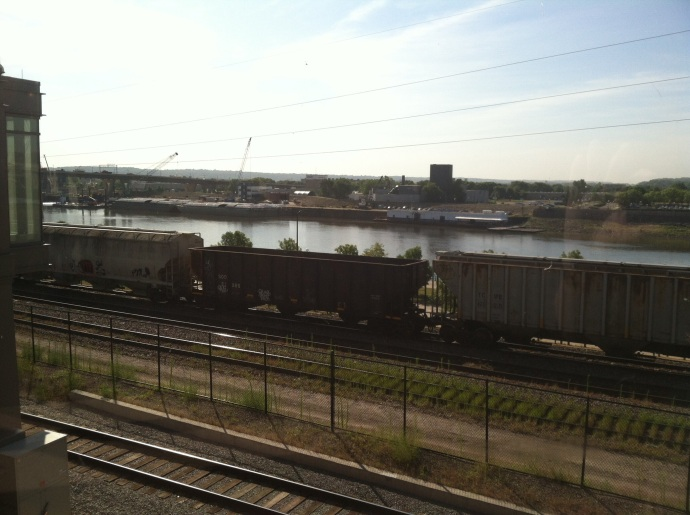 View of trains and barges on the Mississippi RIver at St. Paul from Union Depot platform.