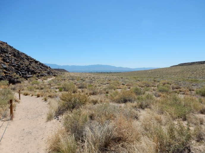 From the back of Rinconada Canyon looking east to Albuquerque, escarpments to left and right, Sandia Mountains in background