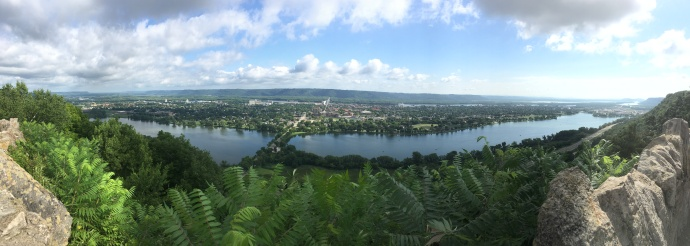 Panoramic view of Winona MN. Wisconsin bluffs in background, then thin blue ribbon is Mississippi River, then City of Winona, then Winona lakes and finally nearest to you the Garvin Heights Bluffs